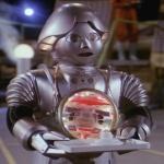 Twiki, de dwaze robot, moet een schijfvormige computer ronddragen en zegt daarbij voortdurend: Biddi-biddi-biddi...